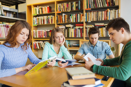 school friends: people, knowledge, education, literature and school concept - students reading books and preparing to exams in library