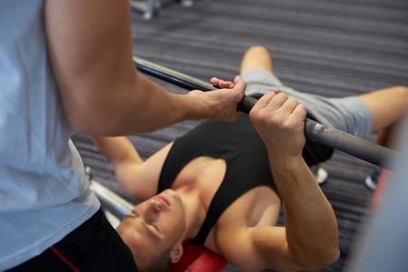 musculos: deporte, gimnasio, trabajo en equipo, levantamiento de pesas y el concepto de la gente - hombre joven y entrenador personal con mancuerna flexionar los músculos en el gimnasio Foto de archivo
