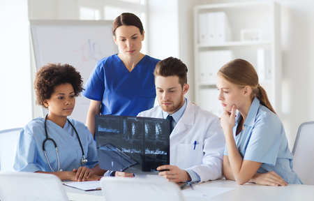 radiology: radiology, people and medicine concept - group of doctors looking to and discussing x-ray image at hospital Stock Photo