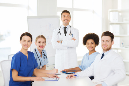hospital, profession, medical education, people and medicine concept - group of happy doctors meeting on presentation or conference at hospital photo