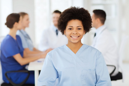medics: clinic, profession, people and medicine concept - happy female doctor or nurse over group of medics meeting at hospital