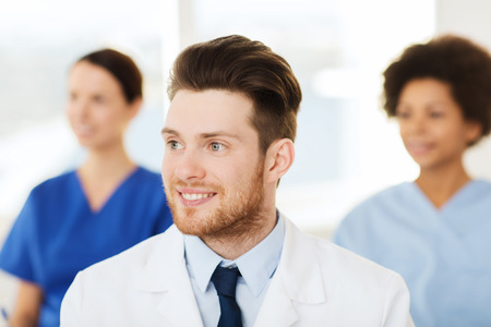 medics: clinic, profession, people and medicine concept - happy male doctor over group of medics meeting at hospital