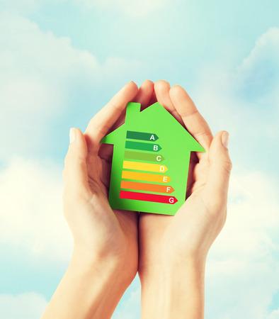 Energieeinsparung, Immobilien und Familie zu Hause Konzept - Nahaufnahme von weiblichen Händen halten grünen Papier Haus mit Energie-Effizienzklasse Standard-Bild