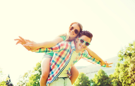 couple having fun: holidays, vacation, love and friendship concept - smiling couple having fun in park Stock Photo