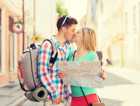 romantic kiss: travel, vacation, love and friendship concept - smiling couple with map and backpack in city
