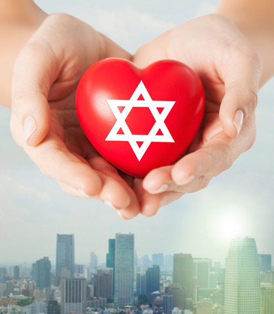 jewish star: religion, christianity, jewish community and charity concept - close up of female hands holding red heart with star of david symbol over city skyscrapers background