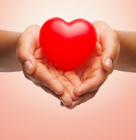 cardiac care: health, medicine, love, valentines day and charity concept - close up of african american female hands holding small red heart over beige background