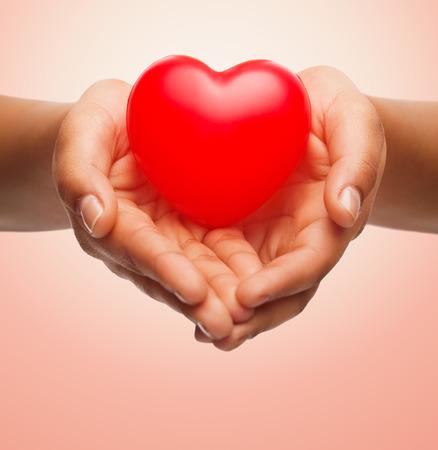 medicale: la santé, la médecine, l'amour, la Saint Valentin et la charité notion - gros plan de mains des femmes africaines américaine tenant petit coeur rouge sur fond beige Banque d'images