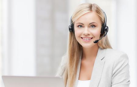 sorridente operatore helpline femminile con le cuffie ed il computer portatile