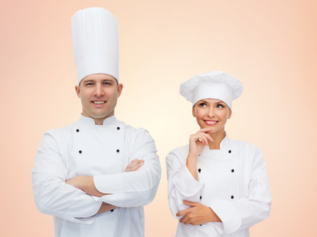 mentors: cooking, profession, teamwork and people concept - happy chefs or cooks couple over beige background