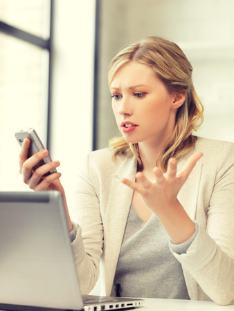 woman angry: Foto de mujer confusa con el tel�fono celular Foto de archivo