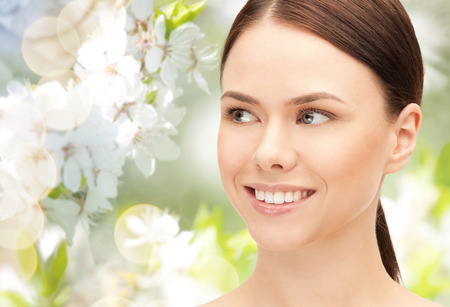 aside: health, people, eco and beauty concept - beautiful young woman face over green blooming garden background