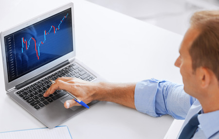 forex: business, office and money concept - smiling businessman working with forex chart in office