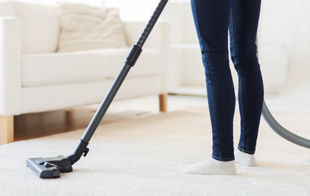 orden y limpieza: people, housework and housekeeping concept - close up of woman with legs vacuum cleaner cleaning carpet at home Foto de archivo