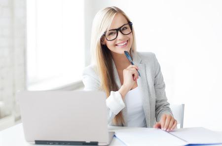 indoor foto van lachende vrouw met documenten en pen Stockfoto