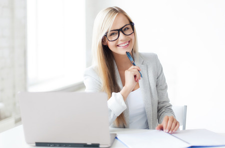 to the secretary: indoor picture of smiling woman with documents and pen