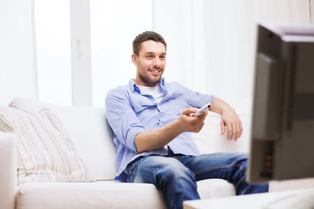 テレビのリモコンの自宅を持つ男の笑みを浮かべて - 家、技術、人、エンターテイメントの概念