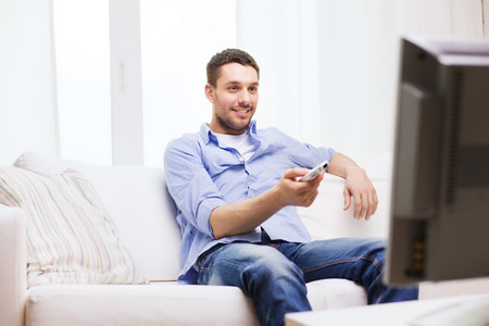 personas viendo television: hogar, tecnología, personas y concepto de entretenimiento - hombre sonriente con el control remoto de la televisión en casa