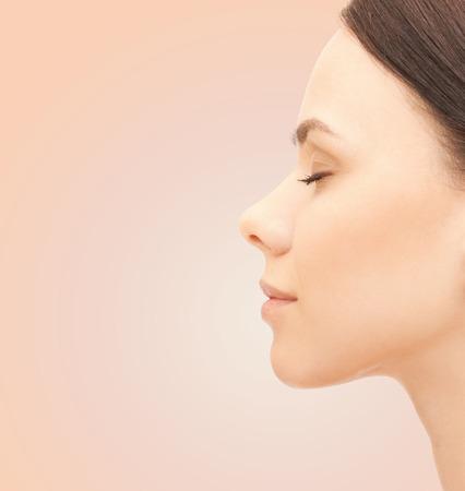 gezondheid, mensen, plastische chirurgie en beauty concept - mooie jonge vrouw gezicht over beige achtergrond Stockfoto