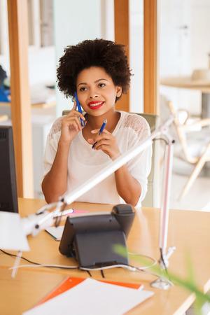 empleado de oficina: negocio, puesta en marcha y la gente concepto - feliz empresaria afroamericana o trabajador creativo que invita al teléfono inteligente en la oficina