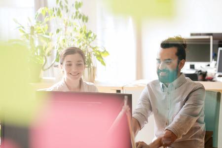 secretaria: negocio, puesta en marcha y la gente concepto - equipo creativo feliz en red con el ordenador en la oficina, dispararon a través de la ventana de vidrio