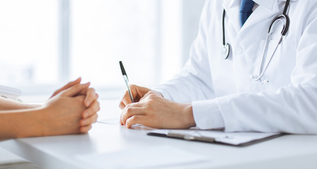family doctor: close up of patient and doctor taking notes Stock Photo