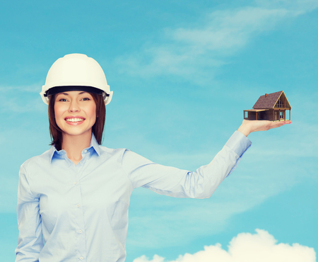 building estate: building, developing, advertising and architecture concept - friendly young smiling businesswoman in white helmet holding house on palm