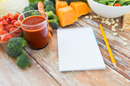 healthy eating, vegetarian food, advertisement and culinary concept - close up of ripe vegetables and notebook with pencil on wooden table Stock Photo