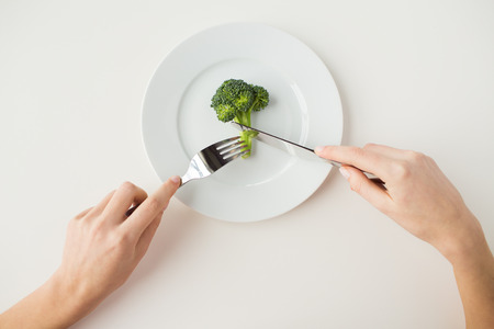 eating up: healthy lifestyle, diet, vegetarian food and people concept - close up of woman with fork and knife eating broccoli