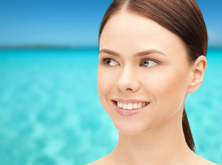 blue sea: health, people and beauty concept - beautiful young woman face over blue sea and sky background