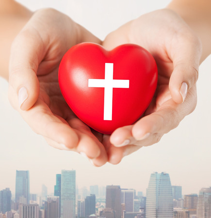 religion, christianity and charity concept - close up of female hands holding red heart with christian cross symbol over city skyscrapers background