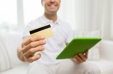 business credit application: technology, people and lifestyle, distance learning concept - close up of happy man with credit card and tablet pc computer at home