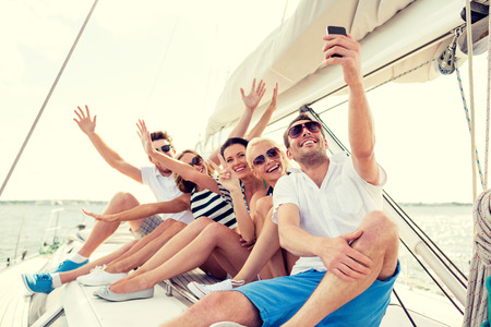 vacation: vacation, travel, sea, friendship and people concept - smiling friends sitting on yacht deck and making selfie