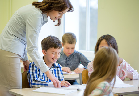 elementary: education, elementary school, learning and people concept - teacher helping school kids writing test in classroom
