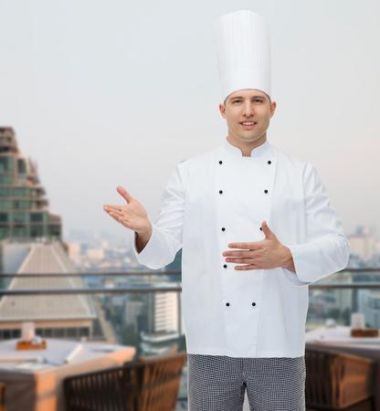 invitando: la cocina, la profesi�n y la gente concepto - feliz cocinero de sexo masculino cocinar invitando sobre la ciudad restaurante lounge de fondo