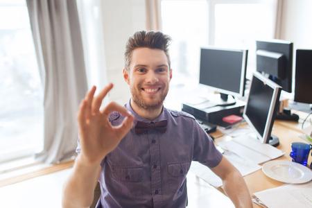 bedrijf, opstarten, gebaar en mensen concept - gelukkig zakenman of creatieve mannelijke beambte met computers zien ok handteken Stockfoto