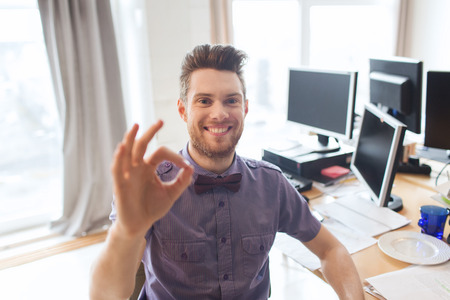 business, startup, gesture and people concept - happy businessman or creative male office worker with computers showing ok hand sign