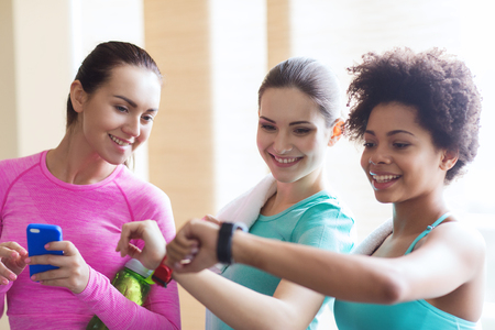watch groups: fitness, sport, training, gym and lifestyle concept - happy women showing time on wrist watch in gym Stock Photo