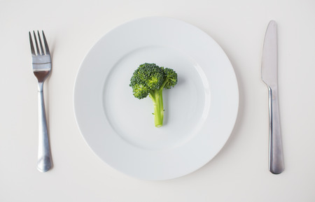healthy eating, diet, vegetarian food and culinary concept - close up of broccoli on plate