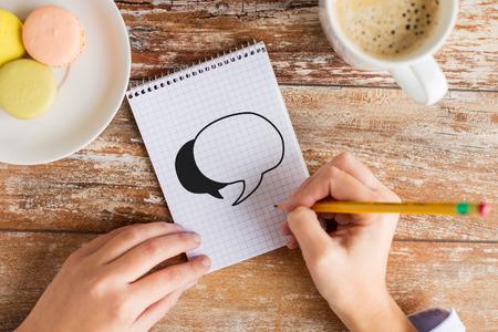 los negocios, la educación y el concepto de la gente - cerca de las manos femeninas con un lápiz, café y galletas de dibujo de la burbuja de texto para el cuaderno en la mesa
