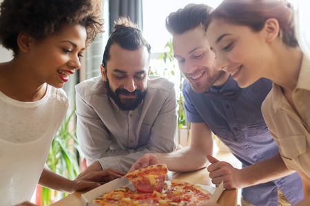 business, food, lunch and people concept - happy business team eating pizza in office Stock Photo