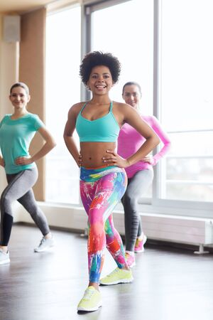 shaping: fitness, sport, training, gym and lifestyle concept - group of happy women working out and stretching leg in gym