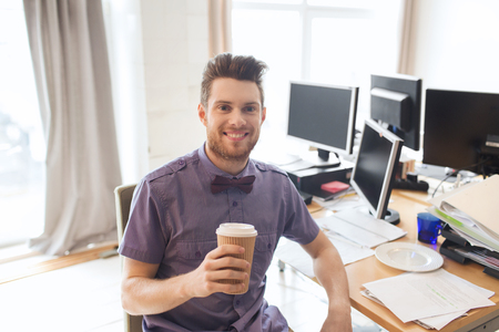 PC: business, startup and people concept - happy businessman or creative male office worker with computers drinking coffee Stock Photo