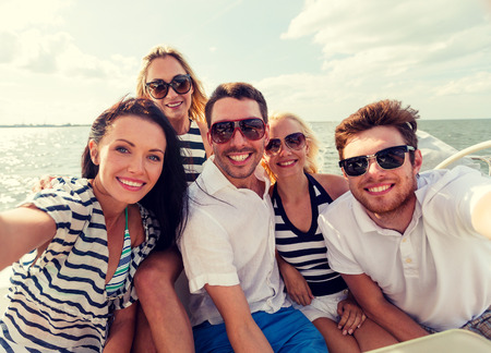 boat: vacation, travel, sea, friendship and people concept - smiling friends sitting on yacht deck and making selfie