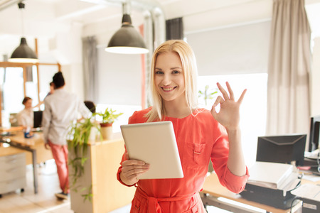 nice smile: business, startup and people concept - happy businesswoman or creative female office worker with tablet pc computer showing ok hand sign
