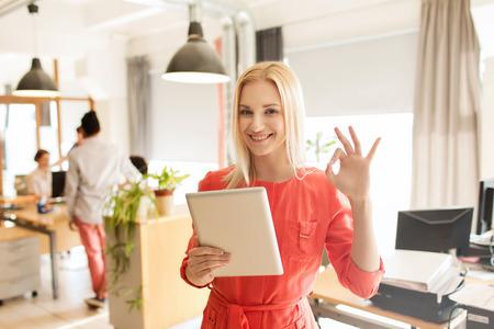 empleado de oficina: negocio, puesta en marcha y la gente concepto - mujer de negocios feliz o trabajador de oficina femenina creativa con el ordenador Tablet PC que muestra signo de la mano ok Foto de archivo
