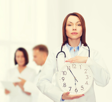 timezone: healthcare and medicine concept - calm female doctor with wall clock and stethoscope Stock Photo