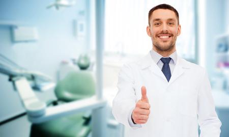 medicina: cuidado de la salud, profesi�n, estomatolog�a y concepto de la medicina - sonriendo dentista masculino que muestra los pulgares para arriba sobre fondo de la oficina m�dica
