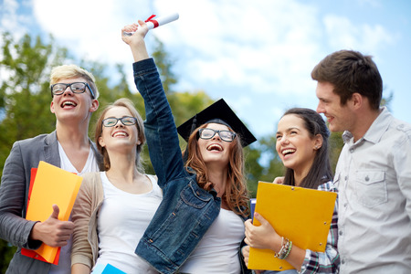 graduation: education, graduation and people concept - group of smiling students in mortarboard with diploma and school folders Stock Photo