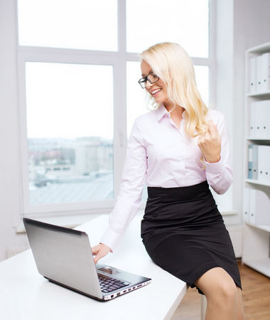 sexy teacher: education, business, flirting and technology concept - smiling businesswoman or secretary with laptop computer sitting on table in office Stock Photo